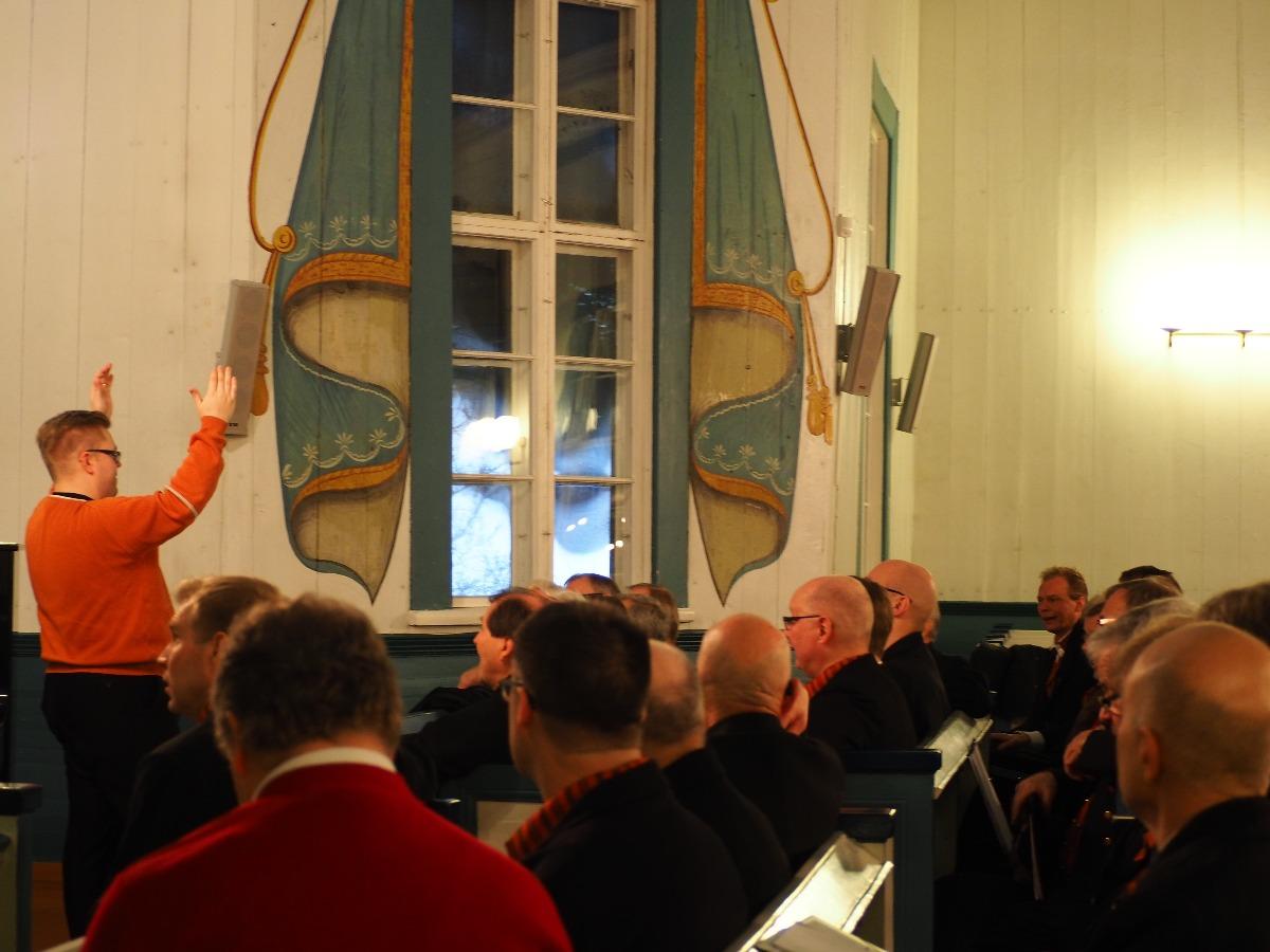 Jussien kuoronjohtaja laulattaa kuoroa.