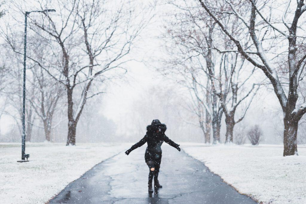 Henkilö kävelee lumisessa puistossa